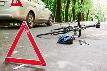 Obraz Place of disaster. Bicycle and silver colored car accident on the road at forest at daytime - fototapety do salonu