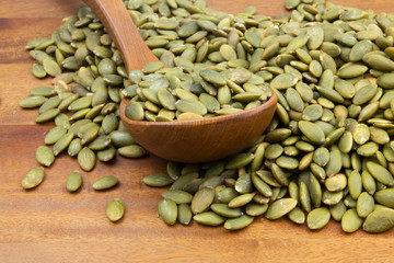 Green pumpkin seeds with wooden spoon on wooden table