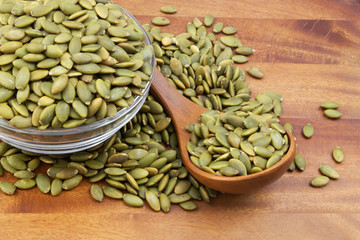 Green pumpkin seeds with wooden spoon and glass bowl