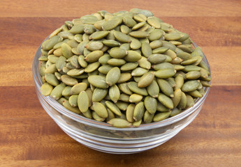 Pumpkin seeds in glass bowl on wooden table