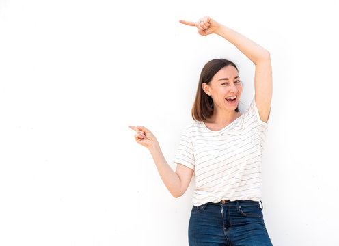 happy older woman with arms raised and pointing to empty space on white background