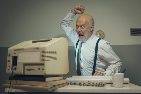 Angry office worker hitting his outdated computer