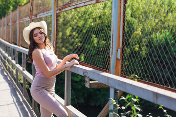 Pretty young woman wearing cowboy hat posing on the old rusty bridge during sunset.