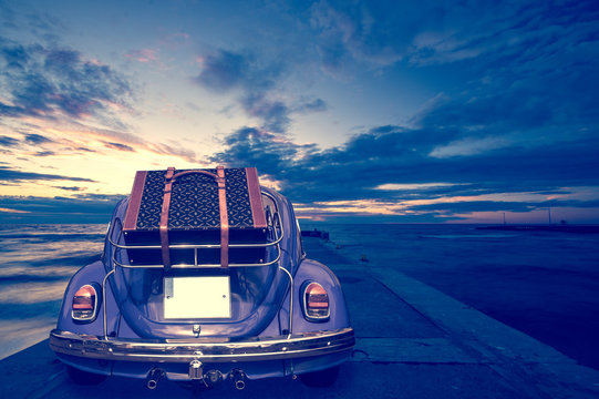 Retro car with luggage on the roof rack on the coastal road. Travel, vacation concepts.retro, vintage color