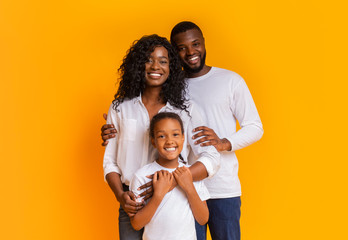 Happy Family Of Three Hugging And Posing Over Yellow Background