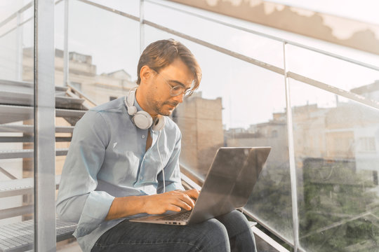 Casual businessman sitting on stairs using laptop