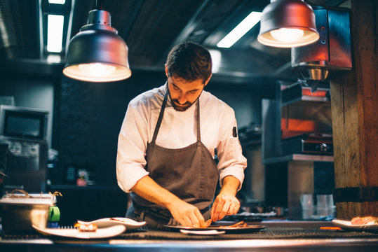 Chef serving food on plates in the kitchen of a restaurant
