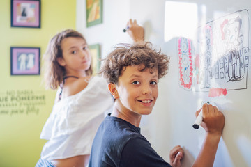 Portrait of smiling boy drawing on a whiteboard with girl in background