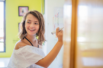 Portrait of smiling girl drawing on a whiteboard