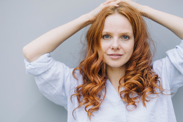 Portrait of beautiful redheaded woman at a wall