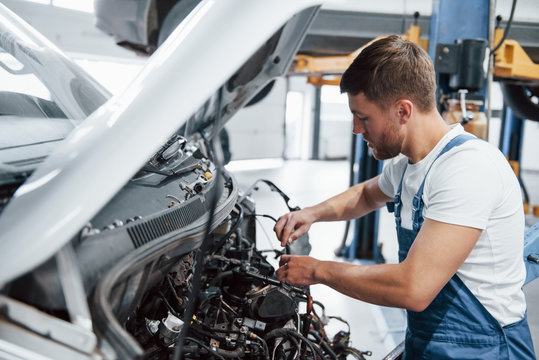 Broken car. Employee in the blue colored uniform works in the automobile salon