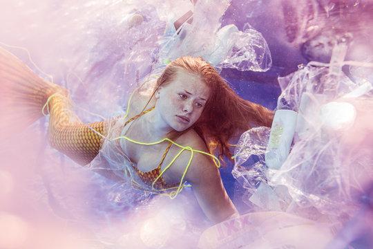 Teenage mermaid girl surrounded by plastic waste under water