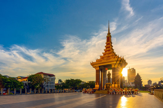 A Statue of King Father Norodom Sihanouk with blue and yellow sky in evening sunset background at central Phnom Penh, Capital of Cambodia. Beautiful cityscape of Cambodia.
