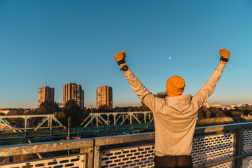 The world is mine. Tomorrow can't wait. I have the power. I can do it. Young fitness male standing on bridge with arms wide open - Stock Image