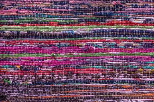 Cloth, typically produced by weaving or knitting textile fibers. Background and texture red old fabric. Closeup