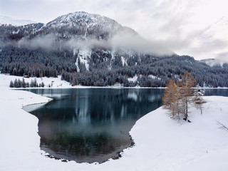 Clouds around snow capped mountain and lake