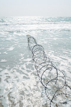 Top angle view of barbed wire running into sea