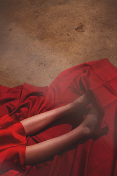 Woman's legs in red shoes lying on red silk