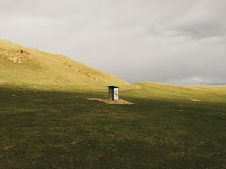 Scenic view of grassland with small metal shed
