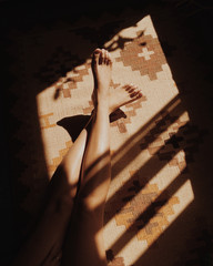 Woman's legs on carpet in sunlight