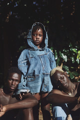 Portrait of girl wearing jacket standing near two shirtless men