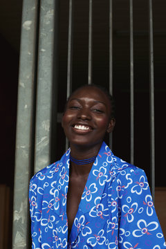 Smiling woman in blue floral shirt standing by metal bars