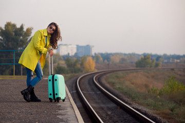 Autumn mood. Travel autumn. Beautiful young girl in a yellow raincoat sits on a suitcase.   girl in a yellow raincoat travels. Autumn train ride. Railway in the fall