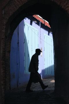 Man walking through shadows under arch