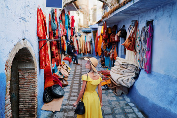 Foto auf Leinwand Marokko Colorful traveling by Morocco. Young woman in yellow dress walking in medina of blue city Chefchaouen.