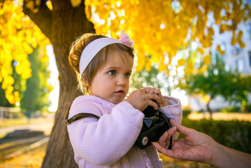 girl photographer. Little girl takes pictures in the autumn park. Autumn Travel Season