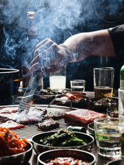 Close up of man preparing meat on small barbecue grill