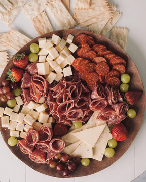Overhead view of meat, cheese and fruits on wooden cutting board