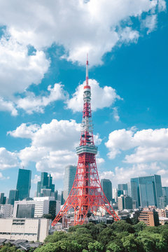 Tokyo Tower in city against cloudy sky
