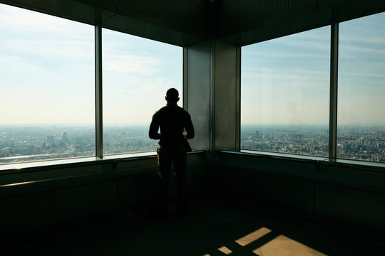 Rear view of man looking at city through window