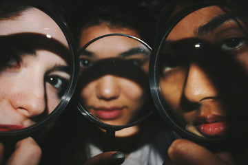 Three faces behind magnifying glasses