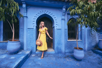 Foto op Plexiglas Marokko Colorful traveling by Morocco. Young woman in yellow dress walking in medina of blue city Chefchaouen.
