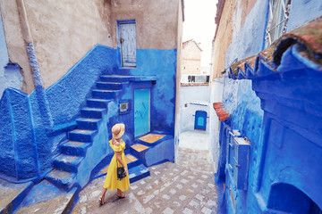 Aluminium Prints Morocco Colorful traveling by Morocco. Young woman in yellow dress walking in medina of blue city Chefchaouen.