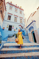 Garden Poster Morocco Colorful traveling by Morocco. Young woman in yellow dress walking in medina of blue city Chefchaouen.