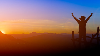 silhouette picture backpacker man show two finger victory sign with lens flare sunset and mountain background twilight time copy space.