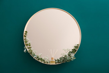 Round mirror with green branches on green wall in modern room interior