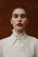 Portrait of model with shaved head and high ruffled collar