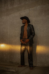 Shirtless model in leather jacket and cowboy hat