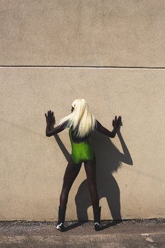 Rear view of model in green swimsuit posing against wall