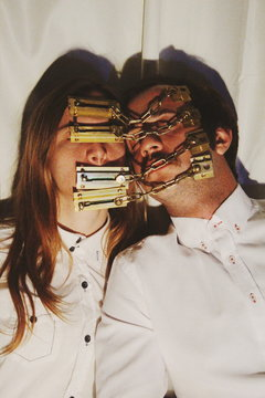 Couple covering their faces with door chain