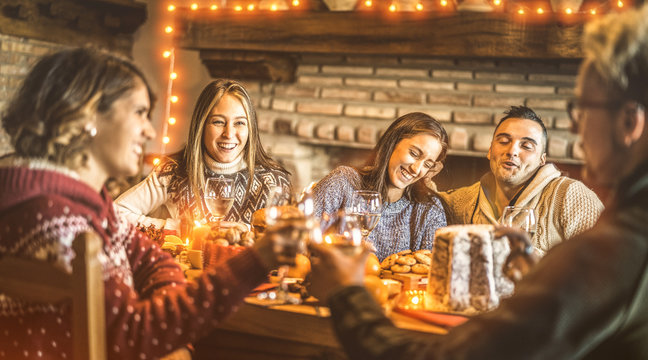 Happy friends tasting christmas sweet food at home fun party - New year's eve mood with white wine glasses toast - Winter holiday concept with young people eating together - Bulb lights warm filter