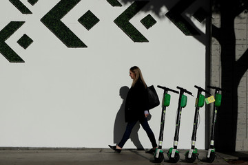 A woman walks past electric Lime scooters parked on the sidewalk in downtown Los Angeles, California