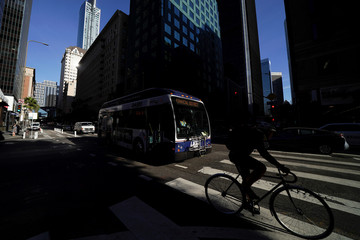 A transit bus and cyclist make their way along a city street in downtown Los Angeles, California
