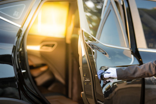 Closeup of Chauffeur opening car door with glove.