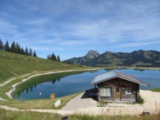 Sudelfeld, Deutschland: Blick auf den Wendelstein und einen malerischen See mit Berghütte Wall mural