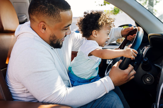 Shot of a little boy sitting on his father's lap in a car and learning to drive. Young parent playing with son in car.